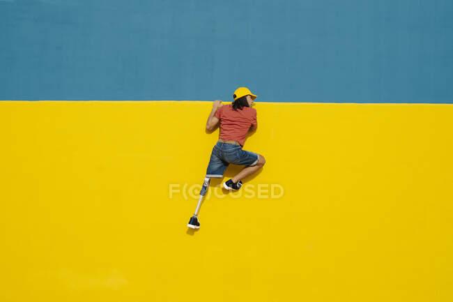 Молодий чоловік докладає зусиль, щоб піднятися по багатокольоровій стіні. — стокове фото