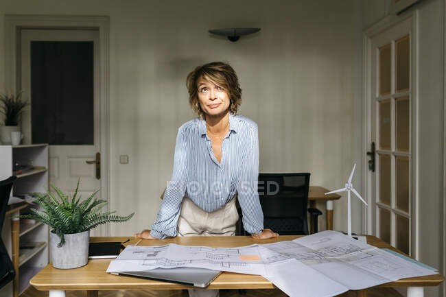 Female engineer leaning on desk while standing in office — Stock Photo