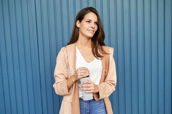 Mujer joven mirando hacia otro lado mientras sostiene la botella reutilizable mientras está de pie contra la pared de metal azul - foto de stock