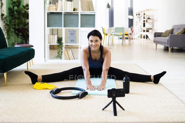 Запись видео с женским влиянием на камеру во время упражнений на растяжку дома — стоковое фото