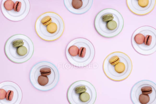 Patrón de platos con coloridas galletas de macarrones - foto de stock
