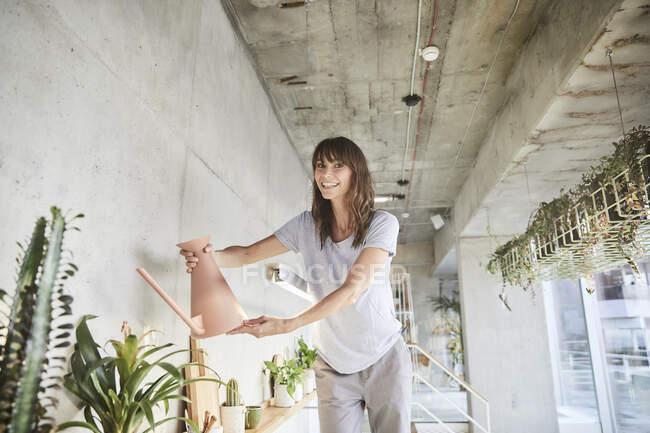 Зріла жінка посміхається, поливаючи домашню рослину. — стокове фото