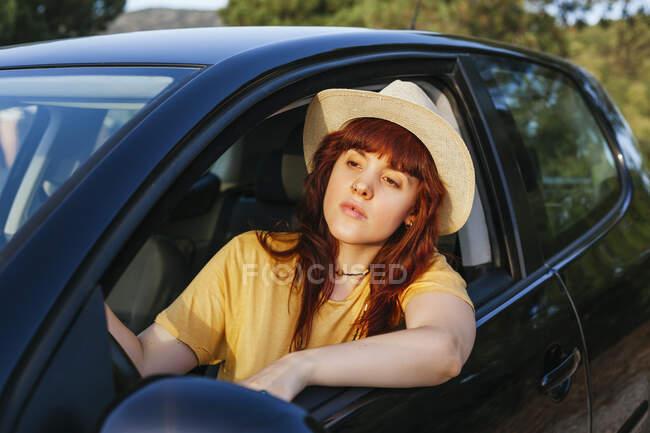 Молода руда жінка, що під час подорожі вигнулася з вікна машини. — стокове фото