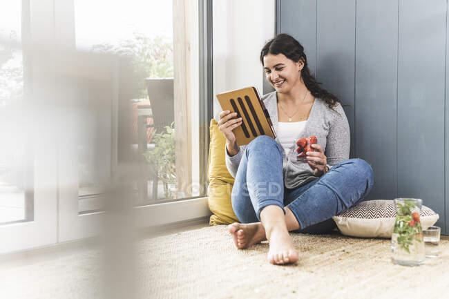 Giovane donna che tiene la fragola durante l'utilizzo di tablet digitale a casa — Foto stock