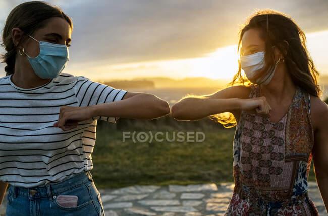 Jovens mulheres em máscaras protetoras cotovelo batendo contra o céu durante COVID-19 — Fotografia de Stock