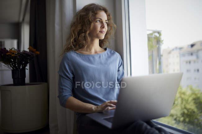 Mujer adulta medio usando el ordenador portátil mientras está sentado en el alféizar de la ventana en casa - foto de stock