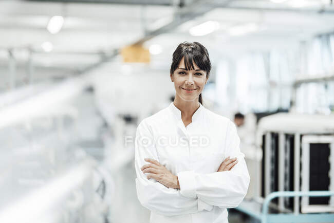 Smiling female scientist standing with arms crossed in bright laboratory — Stock Photo