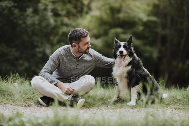 Hombre mirando al perro mientras está sentado en el sendero del arca pública - foto de stock