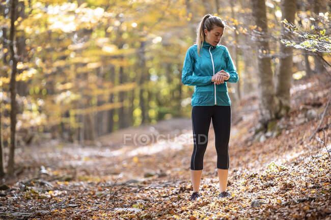Молодий спортсмен пильнує, стоячи в лісі. — стокове фото