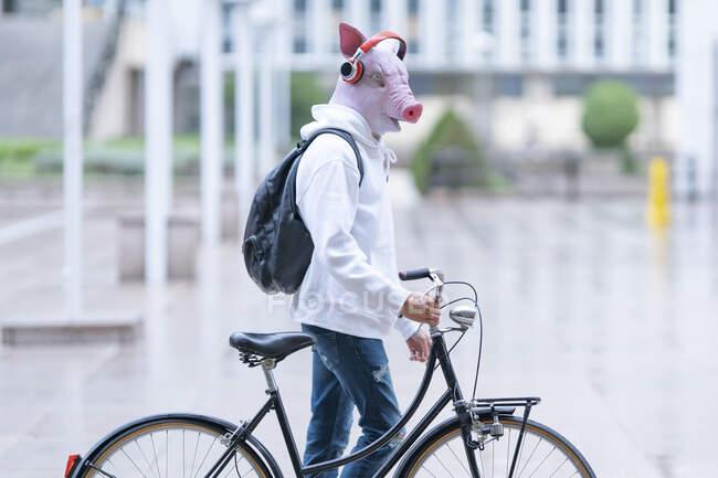 Молодий чоловік з велосипедом у масці свині слухає музику через навушники. — стокове фото