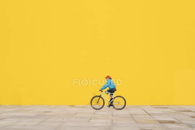 Неповносправний чоловік їде на велосипеді до жовтої стіни. — стокове фото