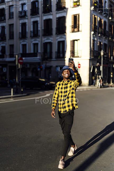Smiling african man using mobile phone while walking in city — Fotografia de Stock