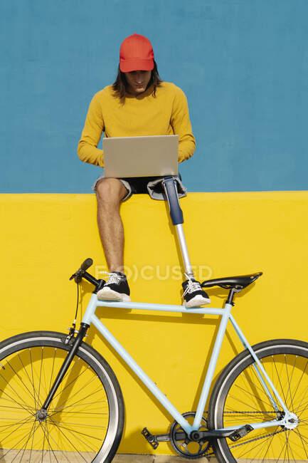 Молодий чоловік з велосипедом працює на ноутбуці, сидячи на багатокольоровій стіні. — стокове фото