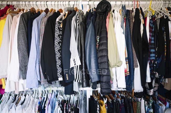 Розмаїття одягу, що висить на стійці в шафі в квартирі. — стокове фото
