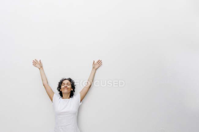 Mujer madura sonriente de pie con los ojos cerrados y los brazos levantados contra la pared blanca - foto de stock