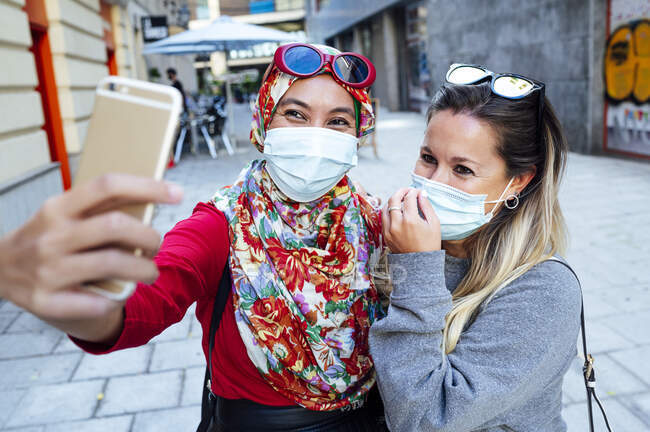 Amigos femeninos multiétnicos tomando selfie mientras usan mascarillas protectoras en la ciudad durante la pandemia - foto de stock