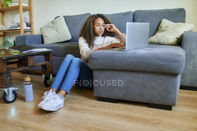 Африканська молода жінка користується ноутбуком, сидячи на підлозі у вітальні. — стокове фото