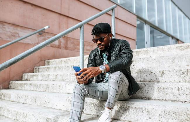 Homem adulto médio usando óculos de sol usando telefone celular enquanto sentado em passos — Fotografia de Stock