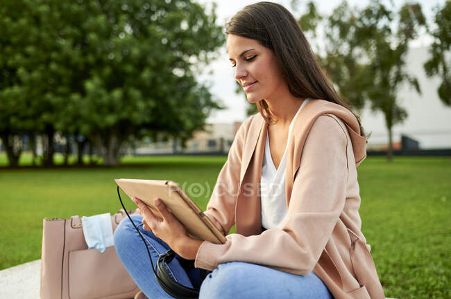 Souriant jeune femme utilisant tablette numérique assis sur l'herbe dans le parc public — Photo de stock