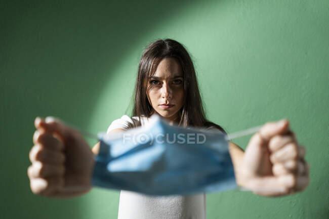 Mulher esticando máscara protetora enquanto estava contra a parede verde durante a crise COVID-19 — Fotografia de Stock