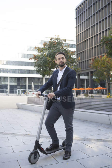 Männlicher Geschäftsmann mit Elektroroller gegen Gebäude in Stadt — Stockfoto