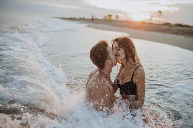 Coppia facendo romanticismo mentre seduto in acqua in spiaggia — Foto stock