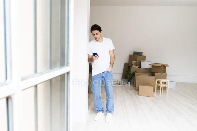 Молодой человек, используя смартфон, опираясь на колонну в новой квартире — стоковое фото