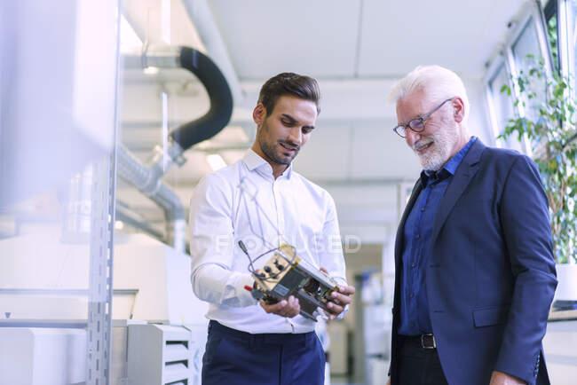 Junger männlicher Ingenieur hält Maschinenteil, während er mit lächelndem Seniorchef in der Fabrik diskutiert — Stockfoto
