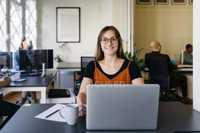 Femme d'affaires confiante et souriante travaillant au bureau — Photo de stock