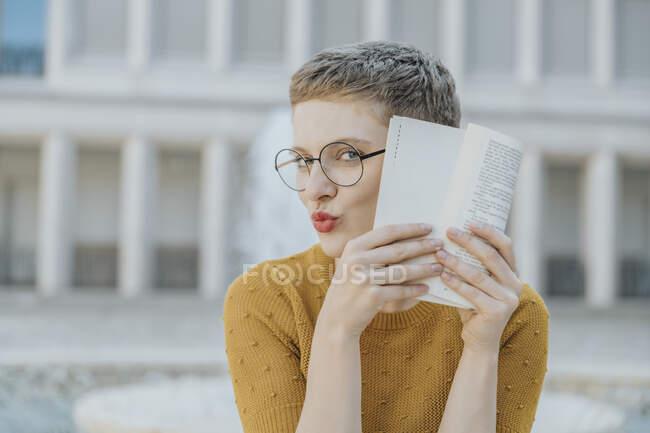 Доросла жінка ховається обличчям до книжки, сидячи в сонячний день. — стокове фото