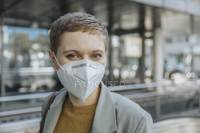 Mujer con máscara protectora de pie en la ciudad - foto de stock
