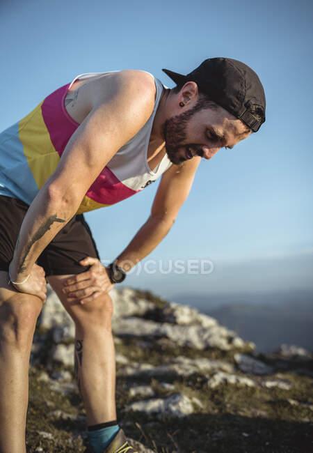 Уставший человек с рукой на коленях стоит на горе против ясного неба — стоковое фото
