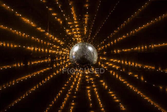 Orange string lights glowing over shiny disco ball — Stock Photo