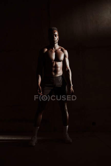 Atleta masculino de pie contra la pared de color gris durante el atardecer - foto de stock