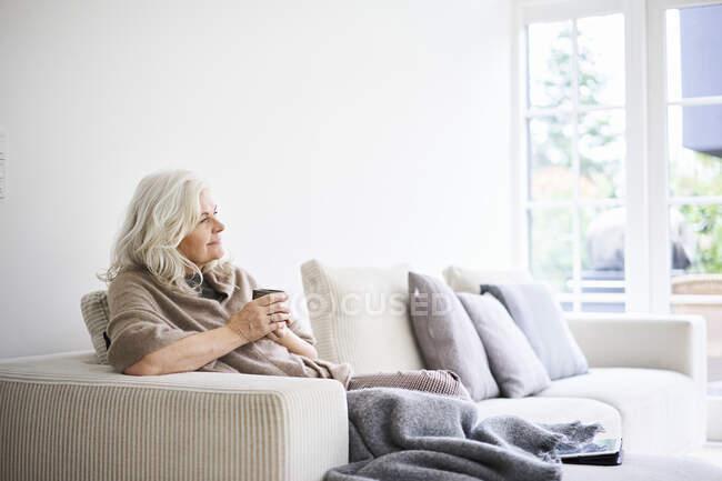 Mujer pensativa con el pelo largo y blanco sosteniendo la taza de café mientras está sentado en el sofá en el apartamento - foto de stock