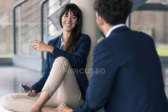 Colleagues sitting on floor in office lobby — Stock Photo