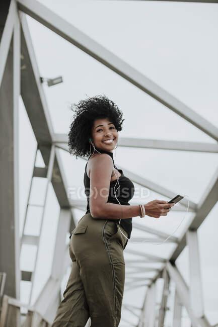 Mujer sonriente escuchando música a través de auriculares parados en el puente de la ciudad - foto de stock