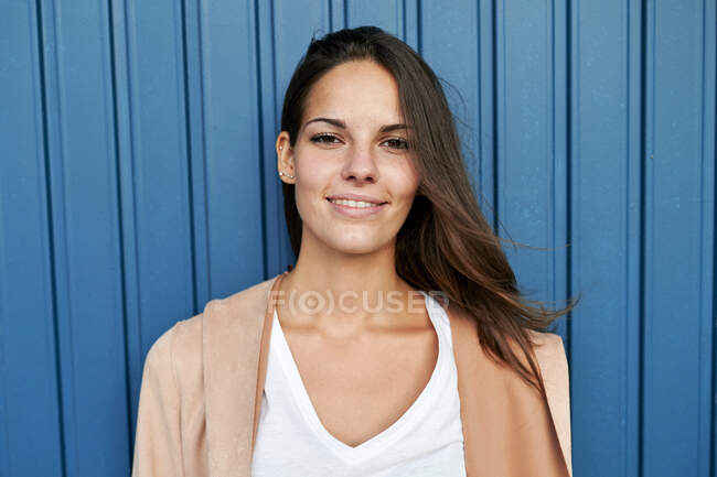 Smiling young woman standing against blue metal wall — Stock Photo