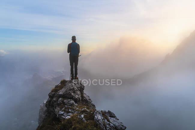 Senderista masculino pensativo de pie en el pico de la montaña durante el amanecer en los Alpes bergamascos, Italia - foto de stock
