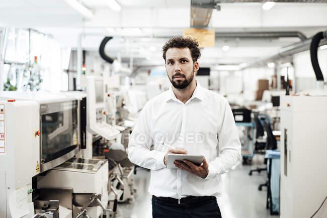 Homme d'affaires confiant tenant tablette numérique debout dans l'industrie lumineuse — Photo de stock