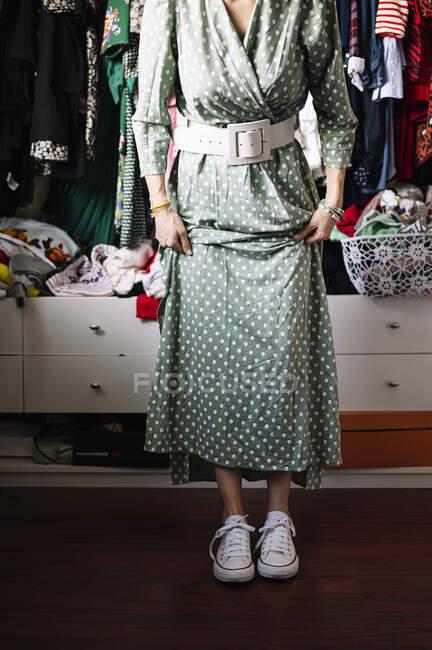 Mulher de vestido verde manchado vestindo sapatos brancos contra roupas penduradas em rack no apartamento — Fotografia de Stock