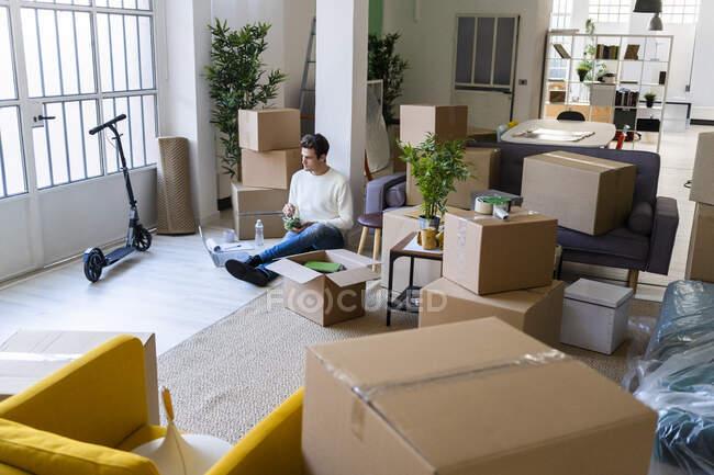 Jeune homme regardant ordinateur portable avec salade assis dans le salon salissant du nouvel appartement — Photo de stock