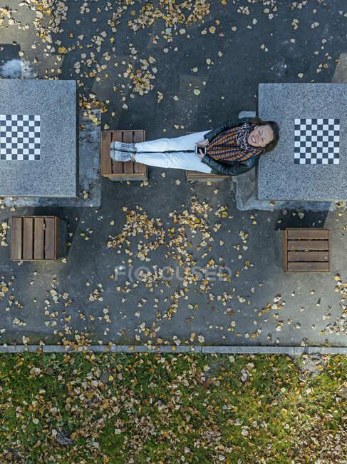 Mujer sonriente relajándose en asientos en medio de mesas de ajedrez en el parque durante el otoño - foto de stock