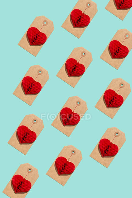 Pattern of labels with heart shaped paper craft decorations — Stock Photo