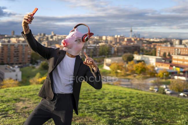 Бізнесмен, одягнений в маску свині і бездротові навушники під час селфі з мобільного телефону на пагорбі. — стокове фото
