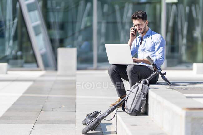 Усміхнений бізнесмен з ноутбуком, який розмовляє по мобільному телефону, сидячи за чемоданом і електричним шутером на кроках. — стокове фото