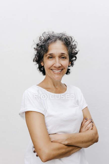 Щаслива зріла жінка стоїть зі схрещеними руками на білій стіні. — стокове фото