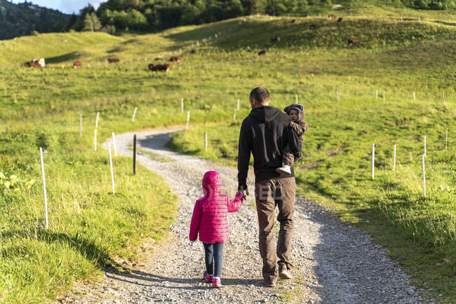 Padre caminando con dos niños en la pasarela del Col des Aravis, Haute-Savoie en el día soleado, Francia - foto de stock