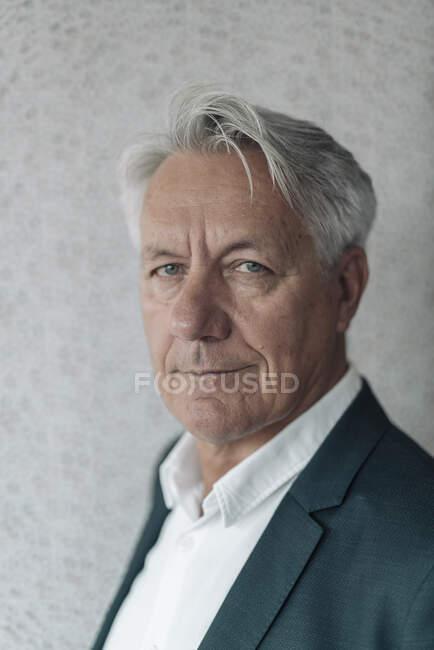 Empresario sonriendo mientras está de pie contra la pared en la oficina - foto de stock
