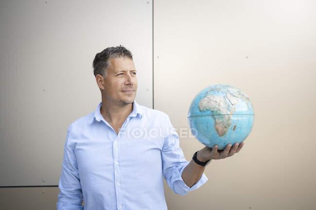 Бізнесмен, що відвернувся, стоячи навпроти стіни. — стокове фото